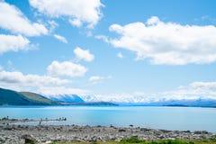 Expansief meningen turkoois water van Meer Tekapo met snow-capped Zuidelijke Alpen achter en toeristen op rotsachtige waterkant royalty-vrije stock afbeelding