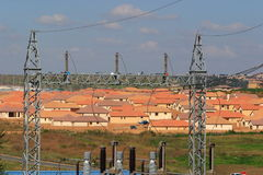 Expansion. Power Substation electricity pole in foreground, houses and cooling towers in the background (Main focus on the poles Royalty Free Stock Photo