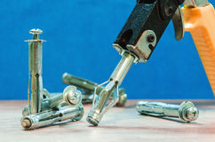 Expansion anchors and construction pistol. Dowels, gypsum wall fastenings and building gun Stock Photo