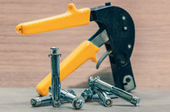 Expansion anchors and construction pistol. Dowels, gypsum wall fastenings and building gun Stock Photos