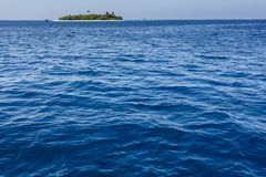 Expansive blue ocean with small tropical island with palm trees viewed in distance Stock Image
