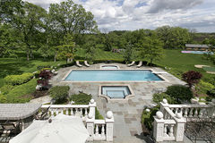 Expansive rear view of luxury home. Expansive view of deck pool and grounds of mansion Royalty Free Stock Images
