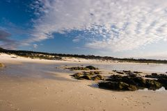 Expansive Sunny Beach. Large sunny beach with a few rocks and a deep blue sky with clouds Stock Images