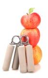 Expansor de dois carpal e uma pilha de três maçãs vermelhas Foto de Stock