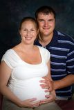 Expectant Couple. In a formal portrait photography session with the women exhibiting the mask of pregnancy stock photo