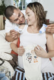 Expectant Couple With Baby Clothes Royalty Free Stock Images