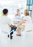 Expectant couple consulting gynaecologist Stock Photos