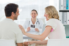 Expectant couple with doctor in clinic Stock Photo