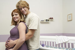 Expectant Couple Embracing By Cradle Royalty Free Stock Photography