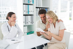 Expectant couple looking at reports in clinic Stock Photo