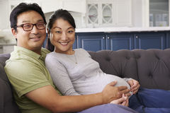 Expectant Couple Relaxing On Sofa At Home Together Royalty Free Stock Image