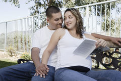 Expectant Couple Sitting On Bench Royalty Free Stock Photos