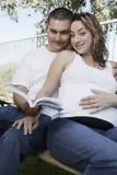 Expectant Couple Sitting On Bench Stock Photo