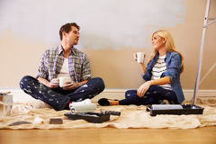 Expectant Couple Taking A Break Whilst Decorating Nursery Stock Photo