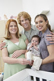 Expectant Couple With Woman And Baby By Cradle Stock Photo