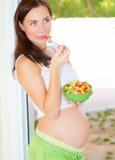 Expectant dziewczyna je warzywa Zdjęcie Royalty Free