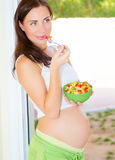 Expectant girl eat vegetables. Beautiful expectant girl eat fresh vegetable salad, pregnant model at home, healthy pregnancy concept royalty free stock photo