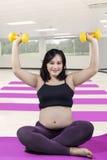 Expectant kobieta ćwiczy z dumbbells przy gym Zdjęcie Royalty Free