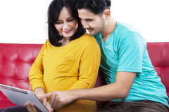 Expectant matka z mężem używa pastylkę Obrazy Stock