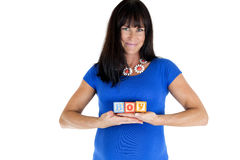 Expectant model holding wooden toy blocks which spell out boy Stock Photo