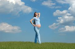 Expectant mother. Pregnant woman on cloudy sky background Royalty Free Stock Photos
