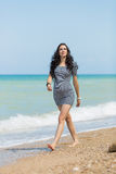 Expectant mother on the beach. Pregnant woman in striped dress walks along seashore royalty free stock photography