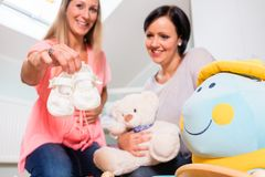 Expectant mother and her friend preparing nursery for baby Royalty Free Stock Photos