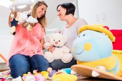 Expectant mother and her friend preparing nursery for baby Stock Photos