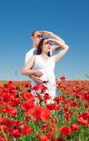 Expectant mother with her husband in poppy field Stock Photography
