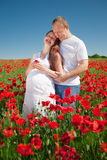 Expectant mother with her husband in poppy field Royalty Free Stock Photos