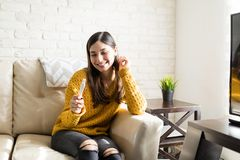 Expectant Mother Holding Pregnancy Kit. Young mother to be looking at pregnancy test kit and smiling while sitting on sofa royalty free stock image