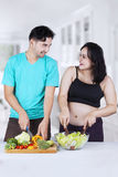 Expectant mother and husband prepare salad Stock Photography