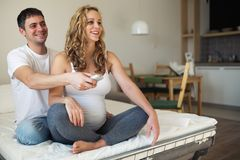 Expectant mother and husband watching tv stock photography