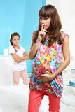 Expectant mother and jealous elder daughter Stock Photo
