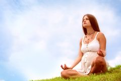 Expectant mother is meditating. Beautiful expectant mother is meditating on open air under blue sky royalty free stock image