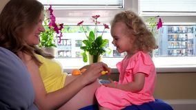 Expectant mother play with her adorable blond daughter on big tummy. Static shot stock footage