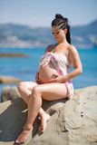 Expectant mother in sarong sits on rock looking on tummy Royalty Free Stock Photos