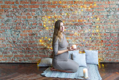 Expectant mother sitting on the floor and holding a candle stock images