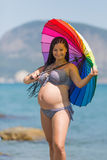 Expectant mother in striped swimwear under rainbow umbrella. Pregnant woman in bikini posing with iridescent parasol against sea. Attractive expectant mother in Stock Image