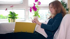 Expectant mother with tablet computer and binder working sitting on bed at home. Expectant mother with tablet computer and binder files working sitting on bed at stock video footage