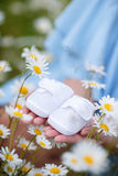 An expectant mother with a white baby booties Royalty Free Stock Photography