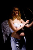 Expectant woman as angel. Pregnant woman dressed in angel's wing and holding bow and arrow stock image