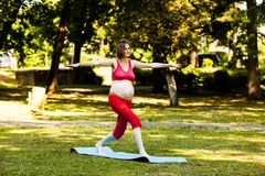 Expectant woman doing fitness exercise outdoor. On a green grass, healthy lifestyle concept stock photography