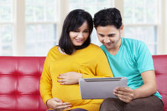 Expectant woman with her husband using tablet Royalty Free Stock Photos