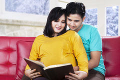 Expectant woman with husband read a book Royalty Free Stock Photo