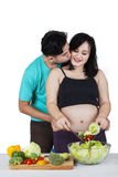 Expectant woman kissed by her husband. Portrait of pregnant mother kissed by her husband when cooking salad stock photos