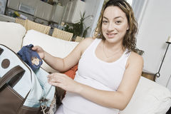 Expectant Woman Packing Baby Clothes Royalty Free Stock Images