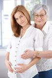 Expectant woman and senior mother smiling Royalty Free Stock Photography
