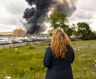 Expectant woman watching a fire in a population. Expectant woman watching a large fire in a population royalty free stock photo