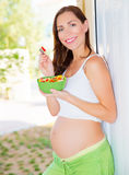 Expectant young lady eat salad royalty free stock photo